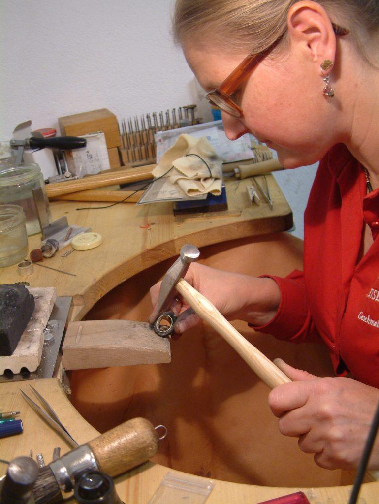 Beispielbilder: mehrer, gemusterte Kupferringe liegen übereinander; Die Goldschmiedin Katharina Böck bei der Arbeit, sie sitz in der Werkstatt an ihren Golschmiede-Tisch