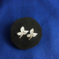 silberne Rosenblatt Ohrstecker vor einem blauen Hindergrund